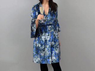 Blue velvet Mayfair dress with frill sleeves, glass of champagne and black shoes and tights