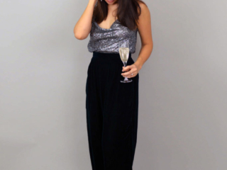 Nina wears Green velvet Portobello Trousers with silver sequinned cowl-neck camisole and holds a glass of champagne