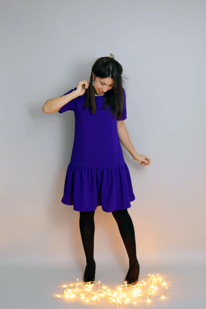 Purple crepe Carnaby dress with gathered skirt with black tights and shoes and fairy lights on the floor